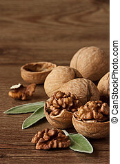 Chopped walnuts. - Walnuts with leaf on a wooden table.