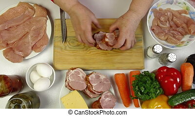 Chopping Bacon - Women's hands slicing pork bacon, an...
