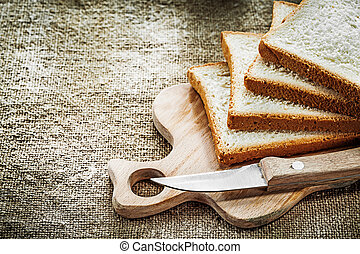Chopping board kitchen knife sliced bread on hessian background