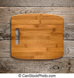 Chopping board on wooden background top view