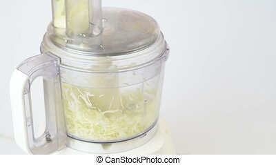 chopping cabbage in a food processor on white
