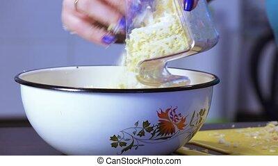 Chopping chicken egg with grater - Brunette girl rubbing...