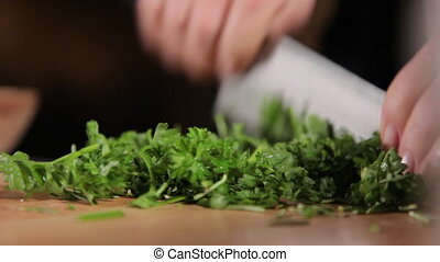 Chopping cilantro in small pieces - A close up shot of...