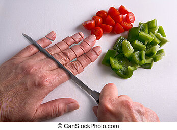 Chopping fingers on cutting board - A human hand is being...