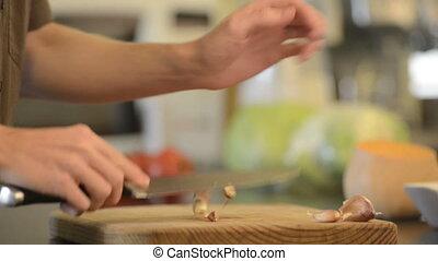 Chopping Garlic - Home cook chopping garlic on a wooden...