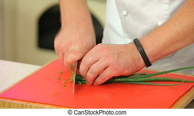 Chopping green onions on a board