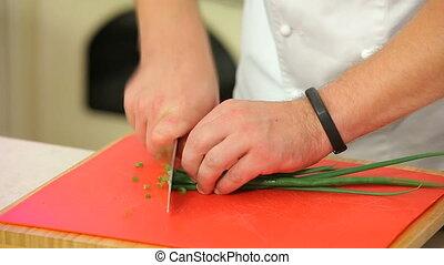 Chopping green onions on a board