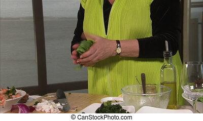 Chopping green vegetable leaves - A medium shot of a woman...