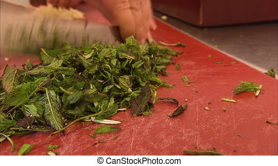 Chopping parsley on red chopping board - A close up shot of...