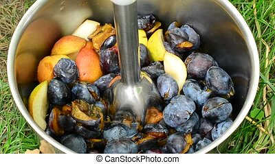 Chopping fruit such as plums and pairs with metallic immersion blender or stick blender to a puree in a metal saucepan outdoors on ground with green grass.