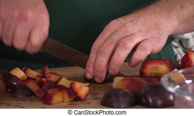 Chopping plums in cubes - A medium shot of a man in green...