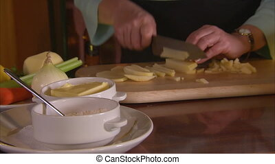 Chopping potatoes in strips - A close up shot of a girl that...