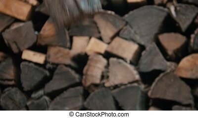 Chopping wood with an axe in woodpile. Mid shot