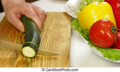 Chopping Zucchini - Women's hands chopping the zucchini in...
