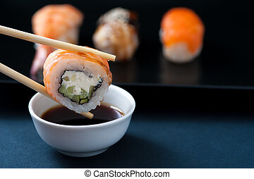 Chopstick with sushi roll and soy sauce, closeup. Popular Japanese cuisine