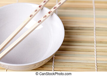 chopsticks and bowl on bamboo placemats