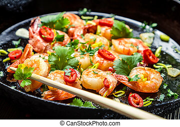 Chopsticks and fried shrimp with herbs