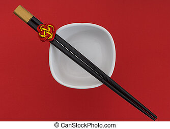 Chopsticks and white bowl on red