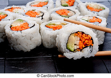 chopsticks holding sushi in front of more sushi on a black textured background