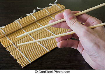 chopsticks in hand in the background of a bamboo sushi mat