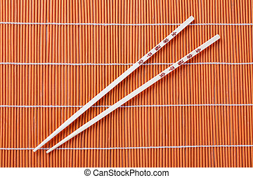 chopsticks - photo shot of chopsticks on bamboo placemats