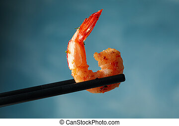 Chopsticks with shrimp on blue background, close up
