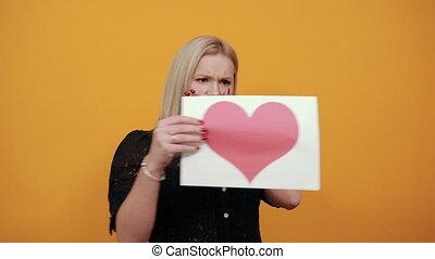 choqué, femme, coeur papier, nerveux, mettre, regarde, irrité, main, rouges, sur, girl, bouche