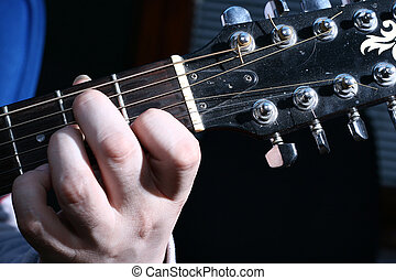chord - closeup image of one hand that plays guitar