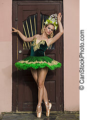 Choreography Concepts. Caucaisan Female Ballet Dancer in Green Tutu Dress and Artistic Flowery Crown Posing In Dance Pose Against Old Wooden Door.Vertical Composition