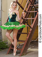 Choreography Ideas. Professional Caucaisan Female Ballet Dancer in Green Tutu Dress Posing In Front of Metal Stairs Outdoors.Vertical Composition