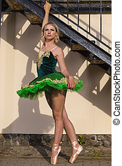 Professional Caucaisan Female Ballet Dancer in Green Tutu Dress Posing In Front of Stairs With Lifted Hand Outdoors.Vertical Orientation