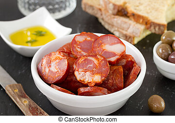 chorizo in bowl with oil and bread