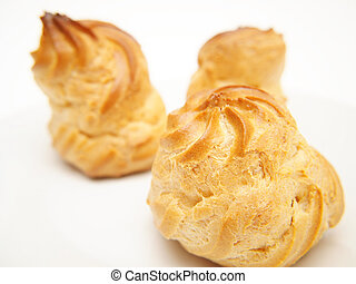 Choux pastry puffs, isolated on a plate, towards white background