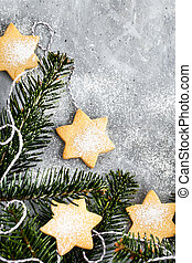 Chrismtas cookie stars and fir tree branches on gray background, holiday concept, top view, copy space