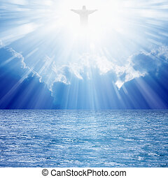 Christ silhouette in blues skies over sea, bright light from heaven