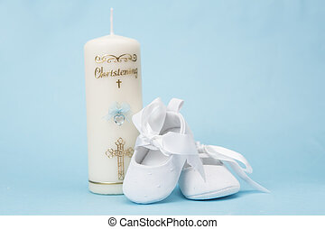 Christening candle for a boy with white baby booties on blue...