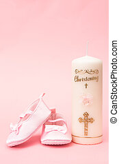 Christening candle with pink baby booties on pink background
