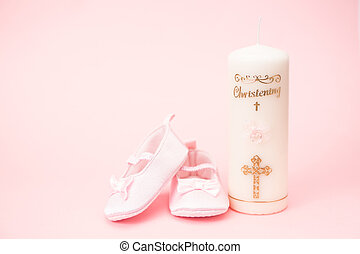 Christening candle with pink baby booties and copy space on...