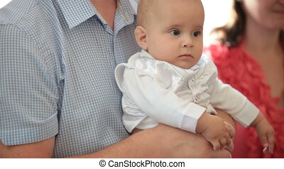 christening - Father holding baby at christening in church