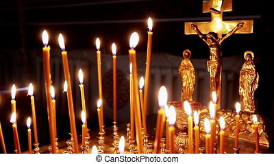 Christian altar - Many candles are lit next to the Christian...