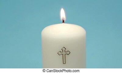 Christian candle burning on blue background