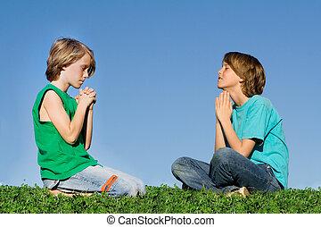 christian children praying outdoors at prayer group or bible camp