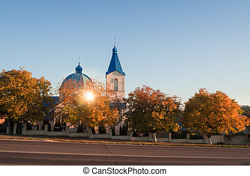 Christian Church on the road in autumn at sunset.
