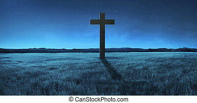 Christian cross in the middle of meadow