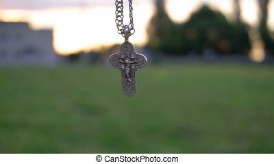 Christian cross on a chain on the background of sunrise