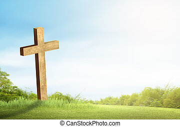 Christian cross on the green grass with sunlight