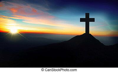 Christian cross on the hill on sunset