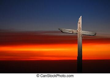Christian cross over dark sunset background