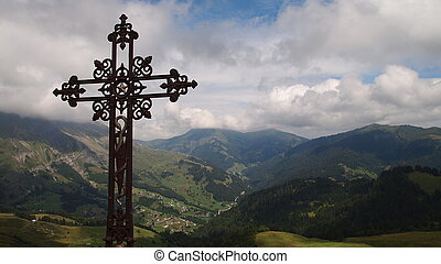 Christian cross with behind a panoramic view of the french mountains from the famous Aravis pass, France, The Alps, Panorama