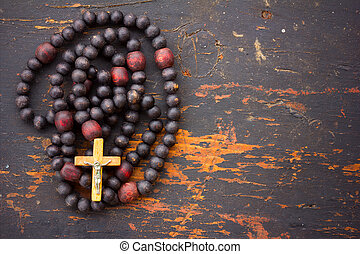 Christian rosary prayer with a cross on old black wooden background with space for text. close-up, top view